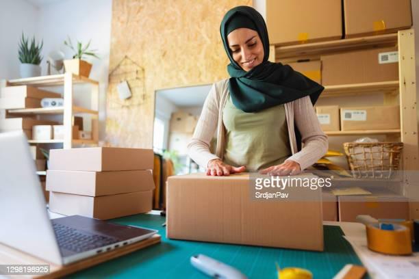moslim onderneemster met hijab die kartondozen voor het leveren aan een klanten voorbereidt - flexplekken stockfoto's en -beelden