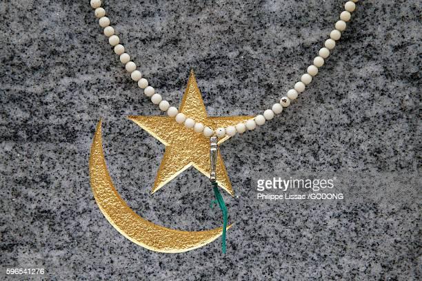 Muslim cemetery in Bobigny, France. Prayer beads on a gravestone.