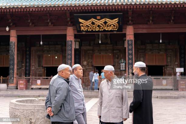 XI'AN SHAANXI PROVINCE CHINA Muslim chat on the square in front of the main hall many of them from other cities such as Yinchuan or Xining come...
