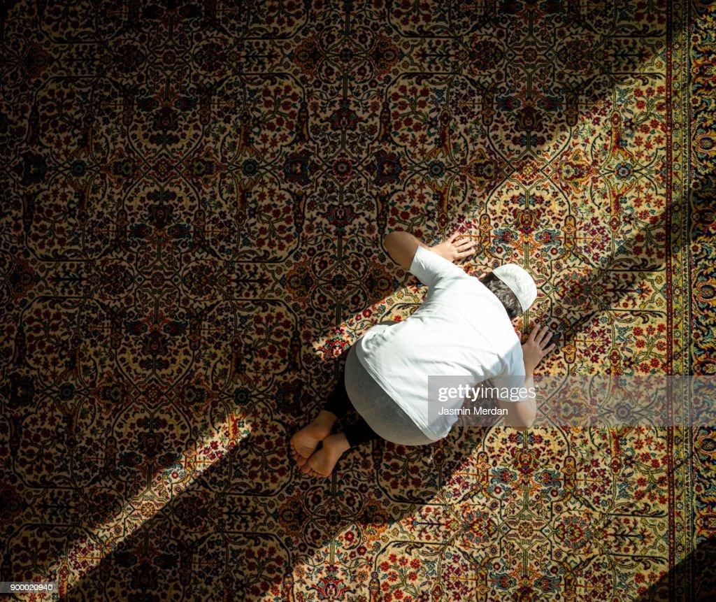 Muslim child inside mosque praying : Stock Photo