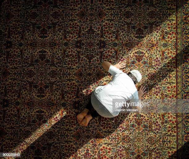 muslim child inside mosque praying - moschee stock-fotos und bilder