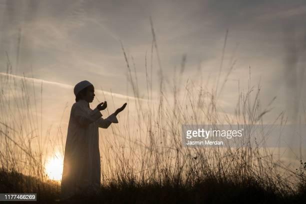 muslim child praying meadow at sunset - allah stock-fotos und bilder