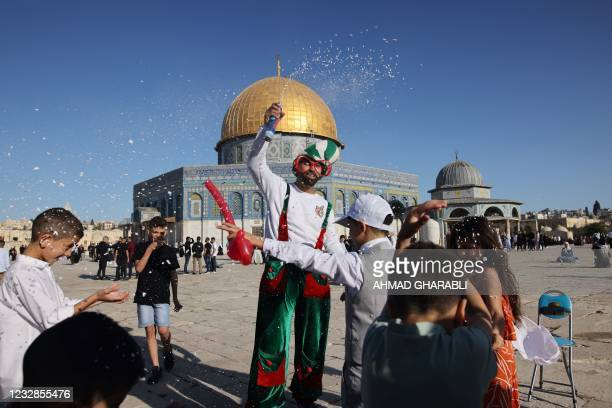 Muslim children celebrate in front of the Dome of the Rock mosque after the morning Eid al-Fitr prayer, which marks the end of the holy fasting month...