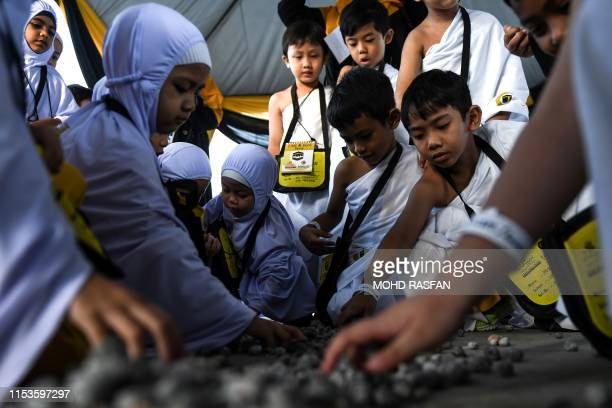 Muslim children clad in white hijab and ihram the respective attire for Muslim women and men performing the Hajj pilgrimage collect mock stones made...