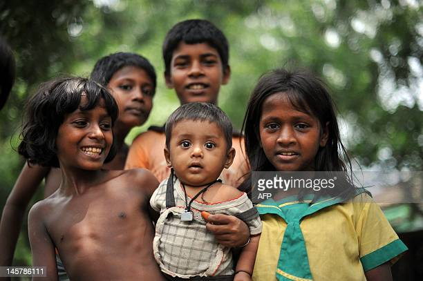 Muslim children pose for pictures outside their house in Sittwe, capital of Myanmar's western Rakhine state on June 6, 2012. An eruption in religious...
