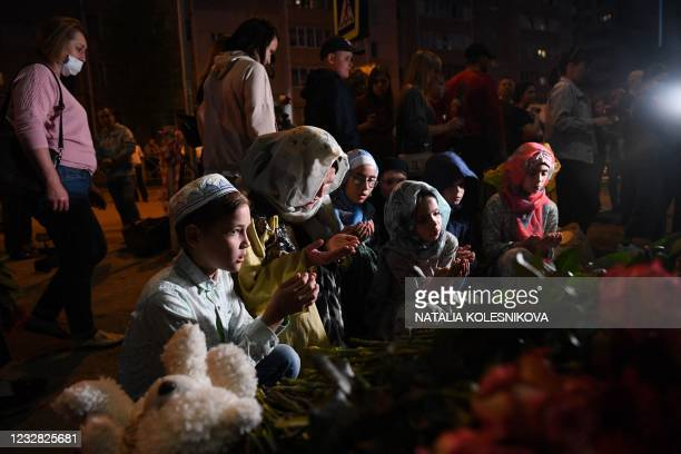 Muslim children pray at a makeshift memorial for victims of the shooting at School No. 175 in Kazan on May 11, 2021. - At least nine people, most of...