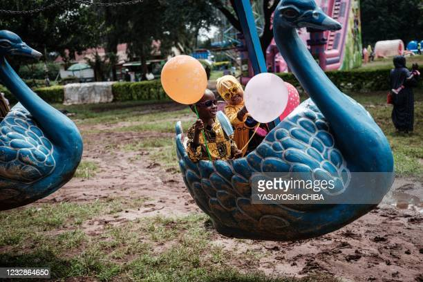 Muslim children ride on an amusement equipment after attending the Eid Al-Fitr prayer that marks the end of the Holy month of Ramadan at Uhuru Park...