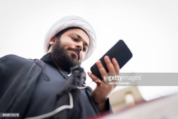 muslim clergy using phone on street - shi'ite islam stock pictures, royalty-free photos & images