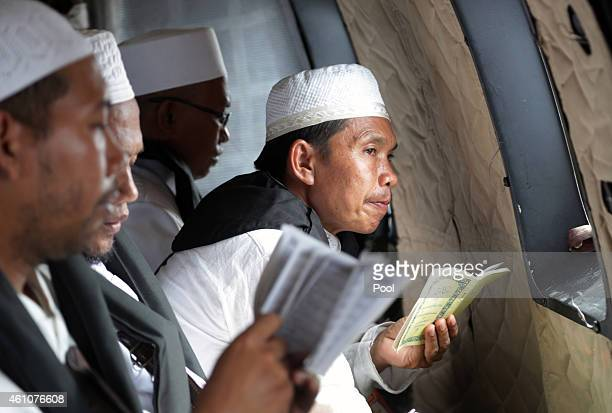 Muslim cleric reads a book of Quran verse during a prayer for the victims of AirAsia Flight QZ 8501 inside an Indonesian Air Force NAS 332 Super Puma...