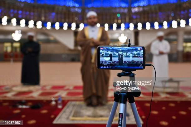 Muslim clerics practice social distancing while reciting terawih evening prayer at the National Mosque broadcast live stream on the first day of the...