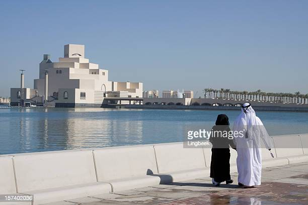 muslim couple along doha corniche - doha stock pictures, royalty-free photos & images