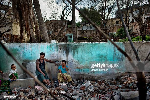 Muslim couple and their son sit on the remains of what used to be their home after waves of violence led against Muslims by Buddhists have destroyed...