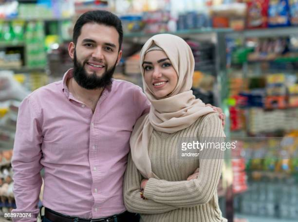 muslim couple at the grocery shop - muslim couple stock pictures, royalty-free photos & images