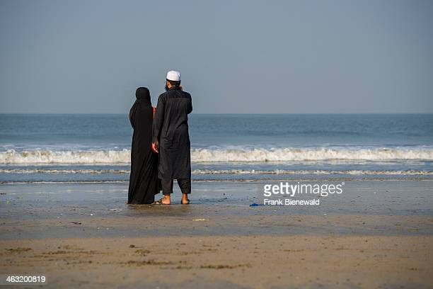 Muslim couple dressed in black cloths are standing at Juhu Beach in the morning