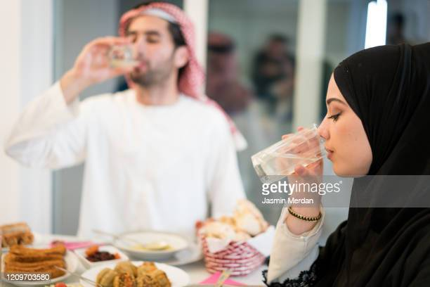 muslim couple drinking water for breaking ramadan fasting - fasting activity stock pictures, royalty-free photos & images
