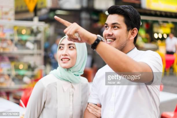 Muslim couple in busy street of Kuala Lumpur city.