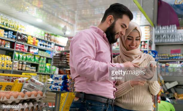 muslim couple shopping at the supermarket using their mobile phone - muslim couple stock pictures, royalty-free photos & images