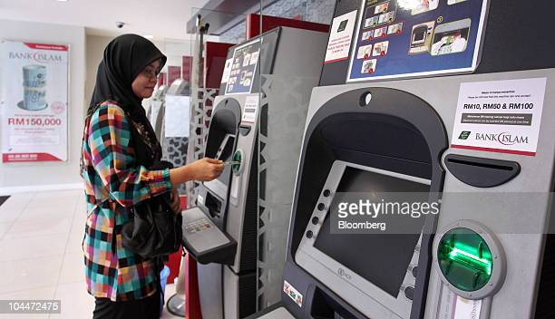A Muslim customer uses the automated teller machine at a branch of BIMB Holdings Bhd formerly known as Bank Islam Malaysia Bhd in Kuala Lumpur...