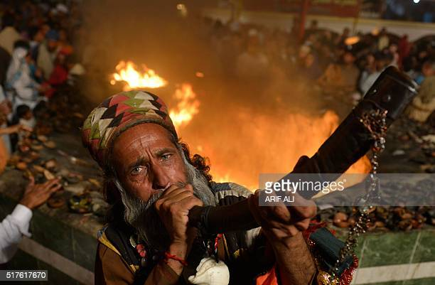 A muslim devotee blows a horn around a fire at the shrine of Sufi saint Hazrat Shah Hussain popularly known as Madhu Lal Hussain during annual...