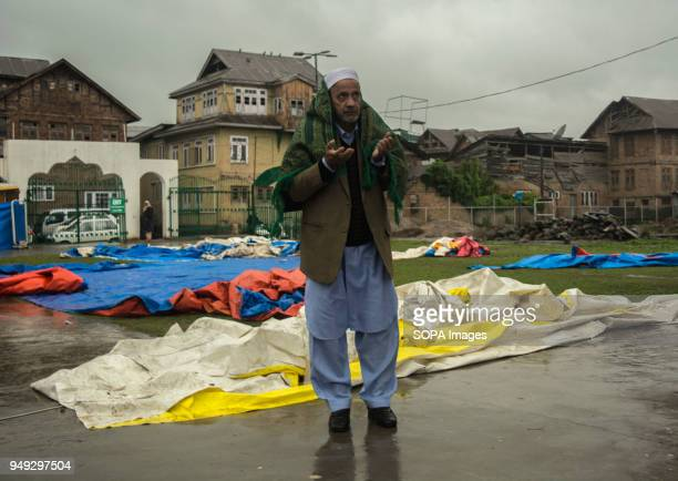 Muslim devotee covered in a prayer mat prays at Hazratbal Shrine Despite incessant rainfall thousands of devotees from across the Kashmir Valley on...