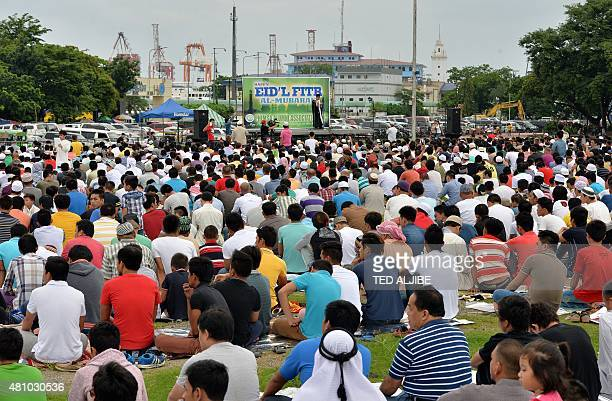 Muslim devotees attend Friday prayers to mark the end of the holy month of Ramadan and the start of Eid alFitr at a park in Manila on July 17 2015...