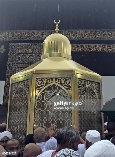 Muslim devotees circumambulate the Kaaba during rain in Mecca Saudi Arabia on August 21 2017 Muslim worshipers tried to collect water with their...