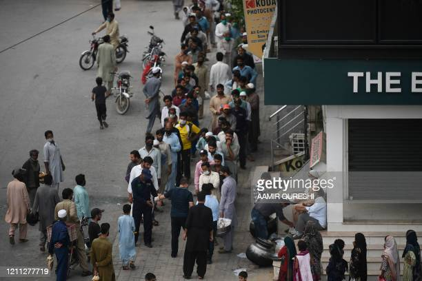 Muslim devotees queue up along a street to collect Iftar food distributed by local residents on the Islamic holy month of Ramadan during a...