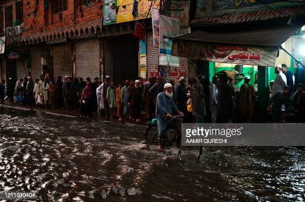 Muslim devotees stands in a queue to collect free Iftar food before breaking their fast along a street on the first day of the Islamic holy month of...