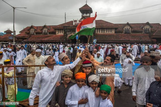Muslim devotees wave Indian National Flag after namaz on the occasion of Eid al-Adha outside Bandra Station on August 12, 2019 in Mumbai, India. The...