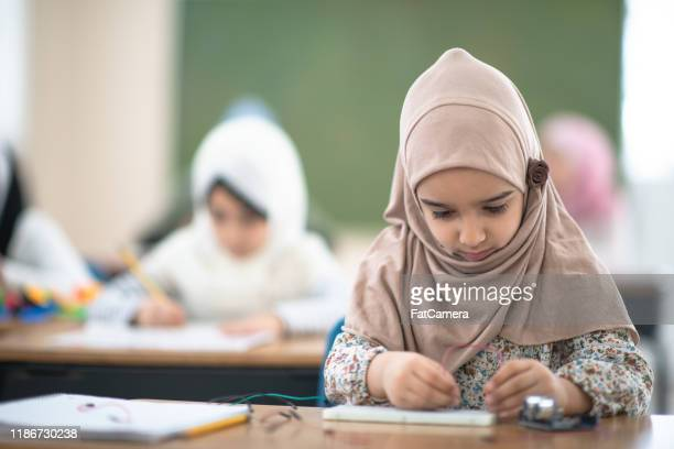 muslim elementary student working on a stem project stock photo - headscarf stock pictures, royalty-free photos & images