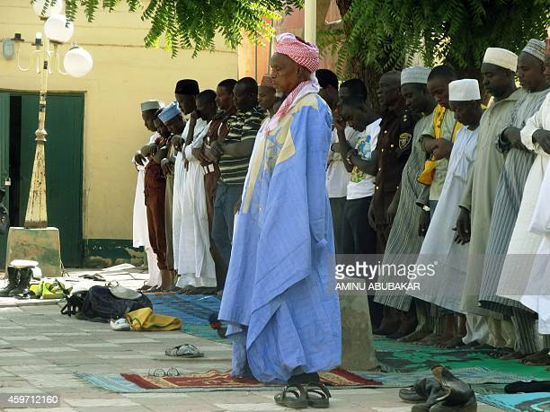 Muslim faithful observe afternoon prayers outside the central mosque in northern Nigeria's largest city of Kano on November 29 a day after twin...