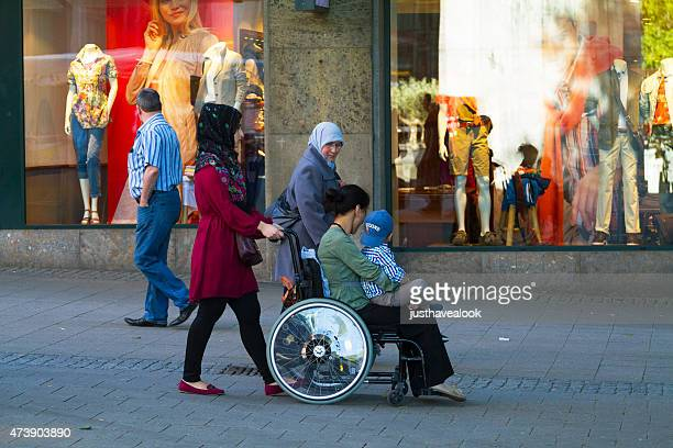 muslim family and woman in wheelchair - islam stock pictures, royalty-free photos & images