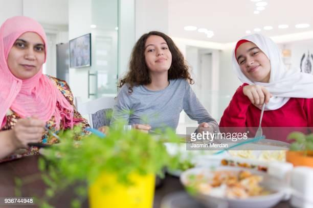 muslim family at dinner table - iftar stock-fotos und bilder