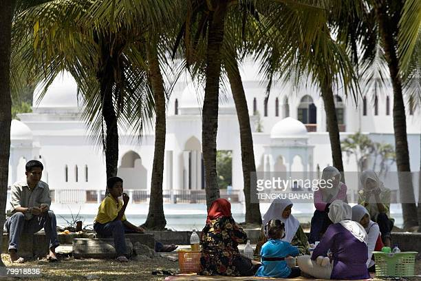 A Muslim family enjoys a picnic underneath coconut trees while the landmark Floating Mosque is seen in the background in Kuala Terengganu eastern...