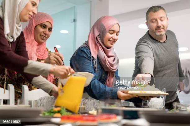 muslim family gathering for iftar food in ramadan - iftar stock-fotos und bilder