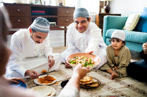 Muslim family having dinner on the floor 1061186560
