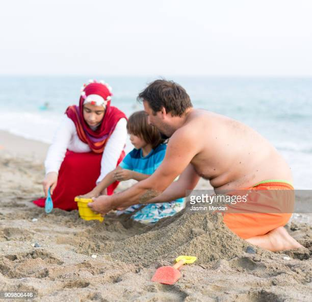 Muslim family in beach sand together