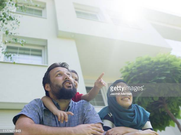 muslim family in front of modern house - middle east stock pictures, royalty-free photos & images