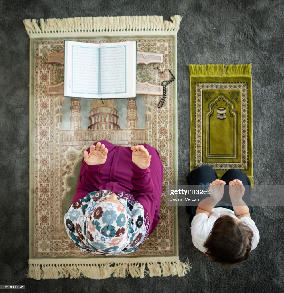 Muslim family in living room praying and reading Koran : ストックフォト