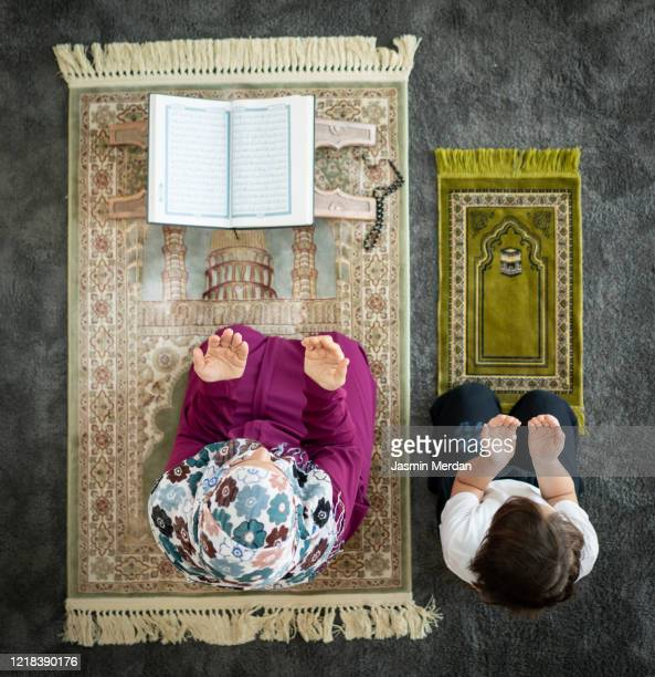 muslim family in living room praying and reading koran - religious celebration stock pictures, royalty-free photos & images