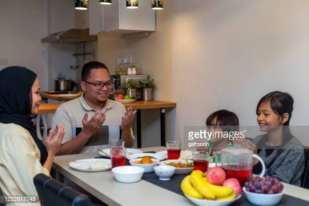 muslim family praying together before breaking fast during the month of ramadan - indonesian culture stock pictures, royalty-free photos & images