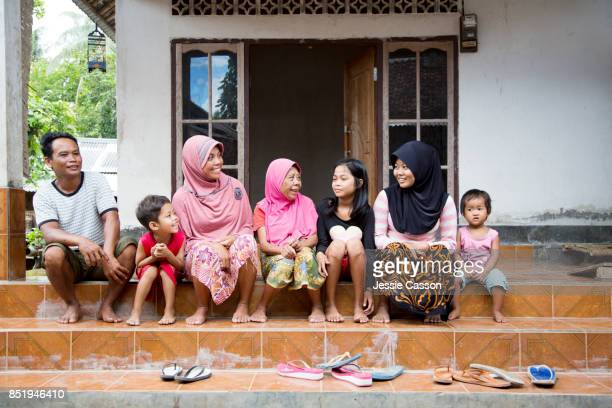 A muslim family sit on the steps outside their home talking and laughing
