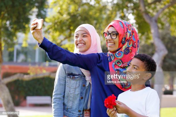 A Muslim family takes a selfie in the park