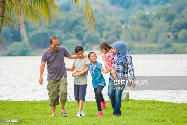 a muslim family walk in a row at the park together. - islam stock pictures, royalty-free photos & images