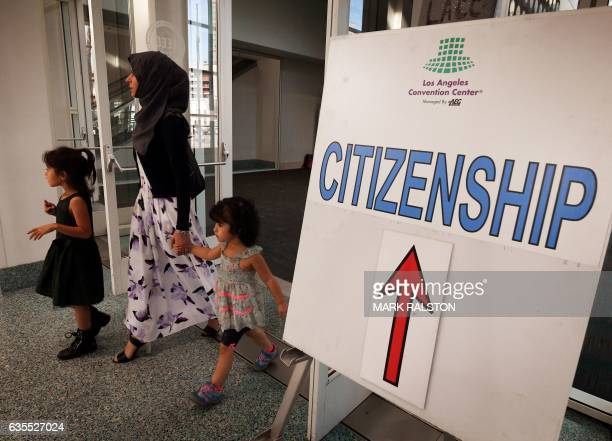 Muslim family walk past a citizenship sign after a naturalisation ceremony for immigrants in Los Angeles California on February 15 2017 Curbing...