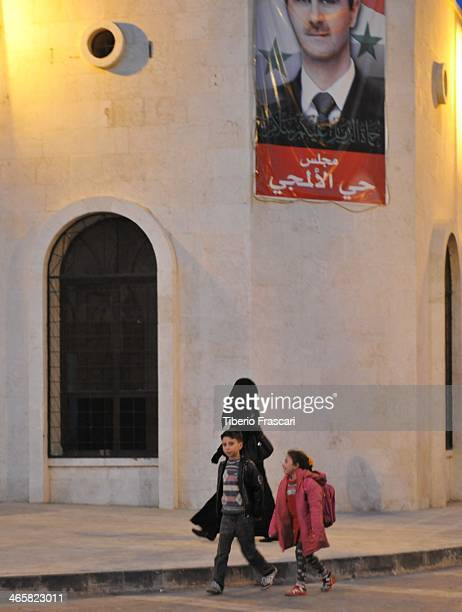 CONTENT] Muslim family walking in Damascus Syria some weeks before the civil warIn the background a portrait of Bashar alAssad