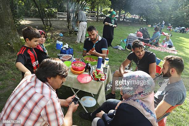 Muslim family who said the did not mind being photographed relaxes over grilled meat and vegetables at a picnic in Boecklerpark in Kreuzberg district...