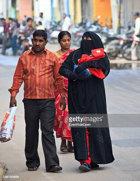 Muslim family woman covered in a black Hijab Burka at December 18 2011 in Mysore Karnataka India