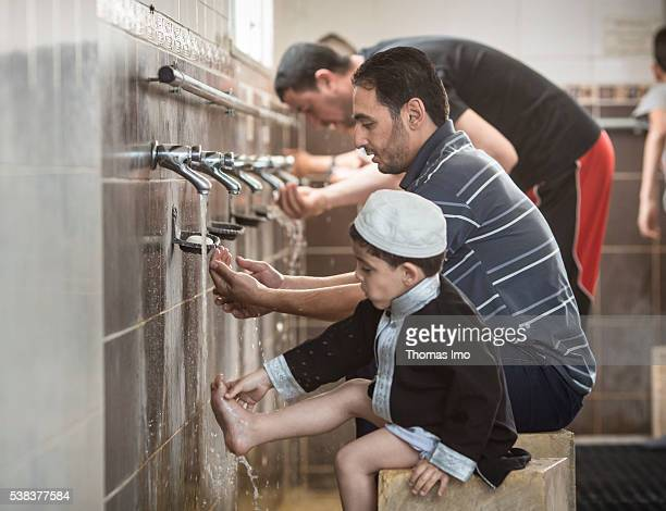 A Muslim father and his little son during the ritual ablution before prayer in the Shishan mosque on April 08 2016 in Sweileh Jordan