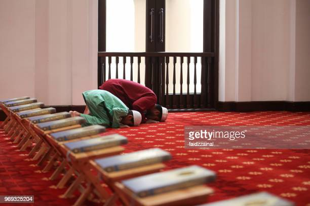 muslim father and son praying together in the mosque - muslim praying stock pictures, royalty-free photos & images
